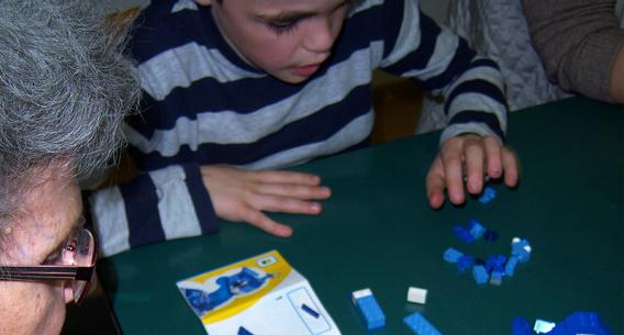 Kind und alte Frau spielen gemeinsam Lego