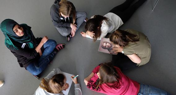 Jugendliche von oben die in einem Kreis sitzen