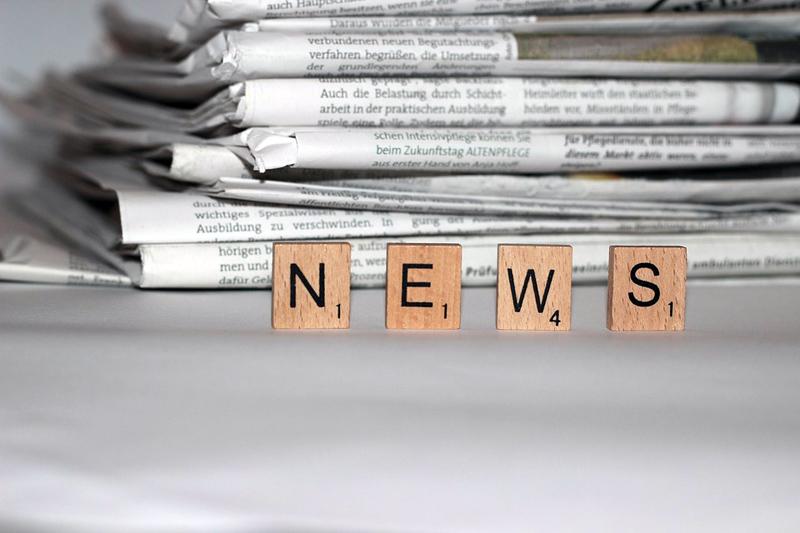 """Holzeckerl mit Buchstaben drauf die """"News"""" ergeben und dahinter ein Zeitungsstapel"""