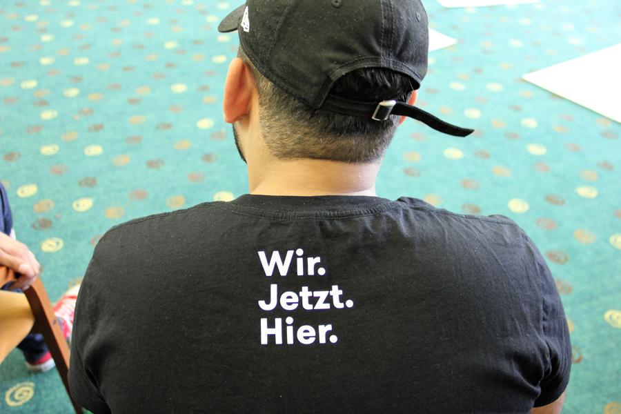 """Jugendlicher mit Rücken zum Bild mit T-Shirt Aufschrift """"Wir. Jetzt. Hier."""""""