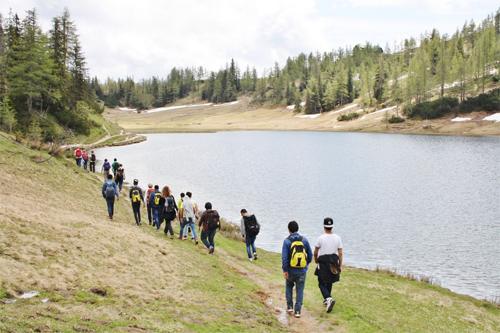 Großer See, Wiesen und Wälder und eine Gruppe von hinten die wandert
