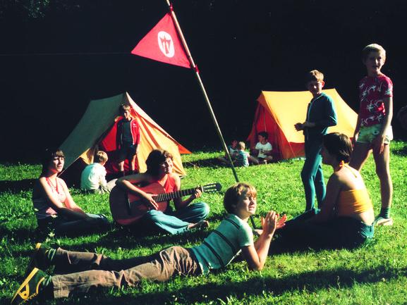 Jugendliche sitzen und liegen auf der Wiese, spielen Gitarre, dahinter Zelte