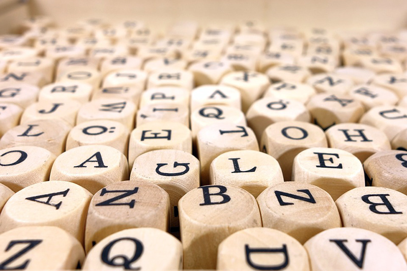 Holzwürfel mit schwarzen Buchstaben drauf
