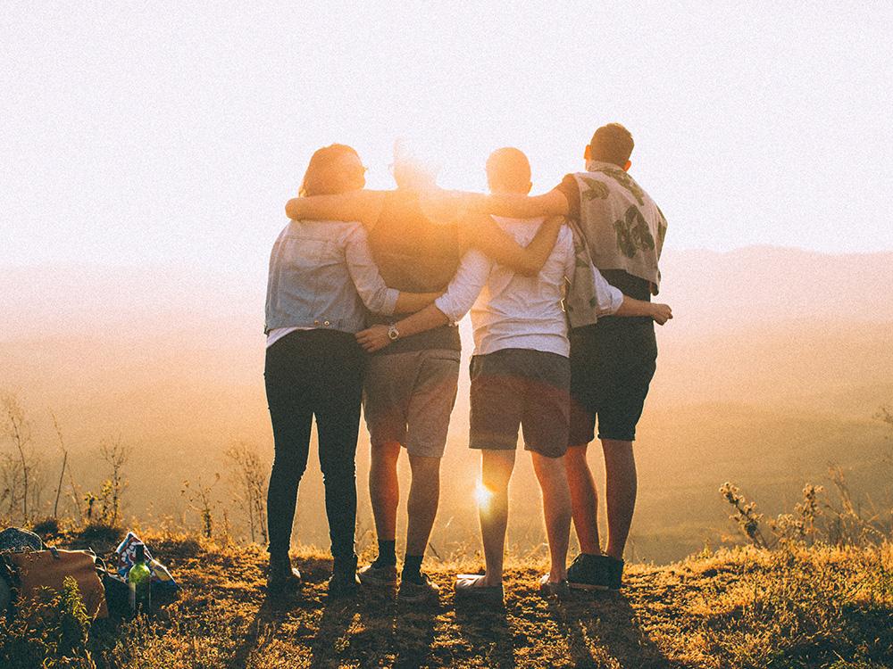 4 Jugendliche stehen in der Natur bei Sonnenuntergang